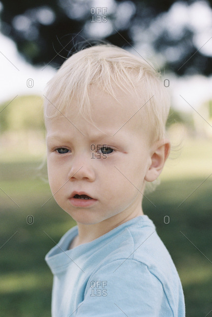 Portrait of a little boy with blonde hair and blue eyes outside