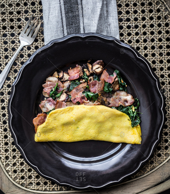 Overhead view of omelet with bacon, mushrooms, spinach and chili flakes