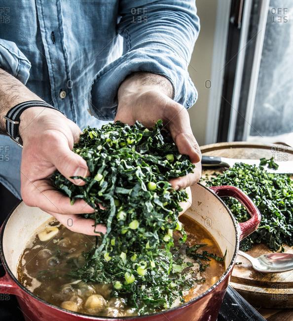 Man adding kale to a pot of Caldo Verde soup