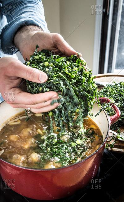 Person adding kale to a pot of Caldo Verde soup