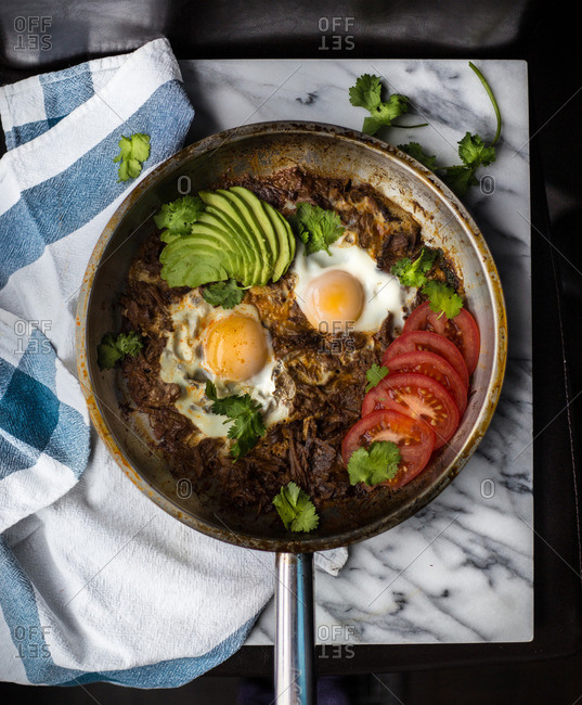 Skillet with pulled-beef, eggs, avocado and tomato