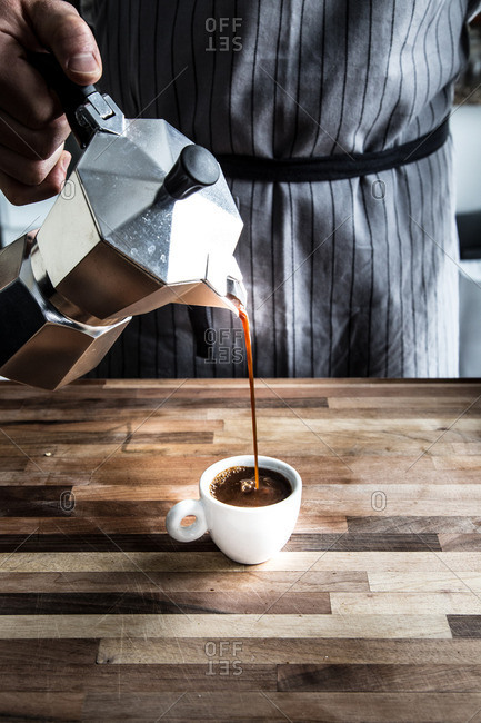 Man pouring espresso into cup on cutting board