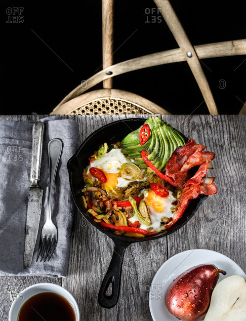 Skillet breakfast with eggs, peppers, avocado and bacon with coffee and pear on side