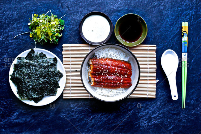 Japanese bbq eel with steamed rice, seaweed, greens and utensils