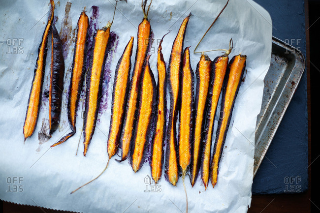 Roasted sliced purple carrots lined on parchment paper and seasoned with oil and salt