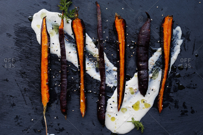 Roasted sliced purple carrots on a slate board overtop tahini with sesame seeds and drizzled oil