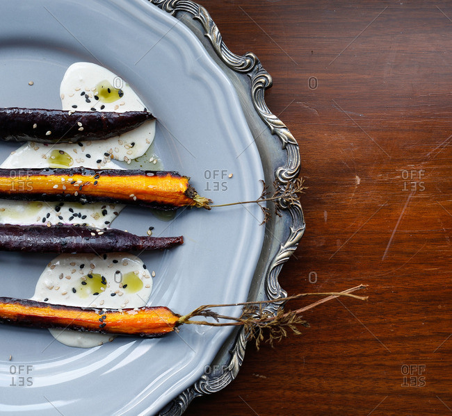 Roasted sliced purple carrots plated overtop tahini with sesame seeds and drizzled oil