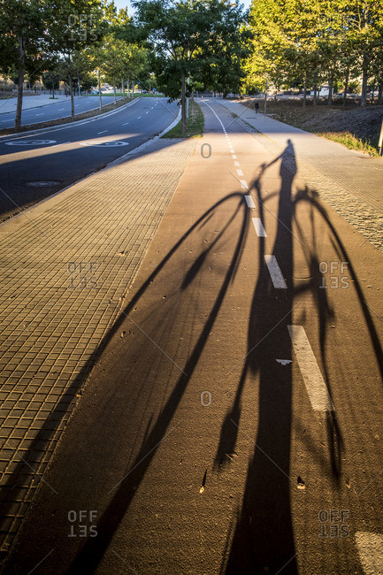 Shadow of person on a bicycle on road, Sant Cugat del Valles, Spain