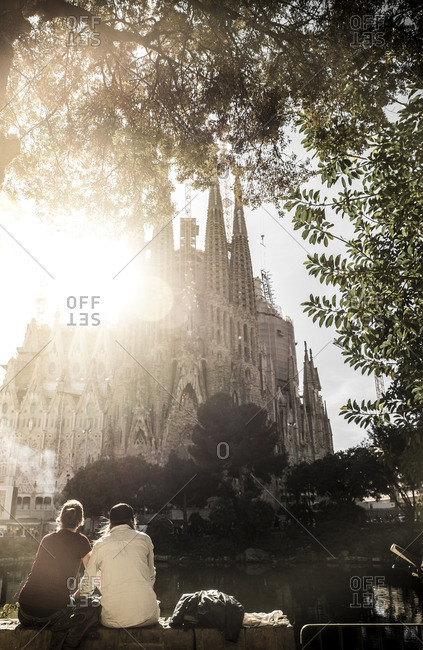 Couple sitting in sight of the Basilica of the Sagrada Familia by Antoni Gaudi, Barcelona, Spain