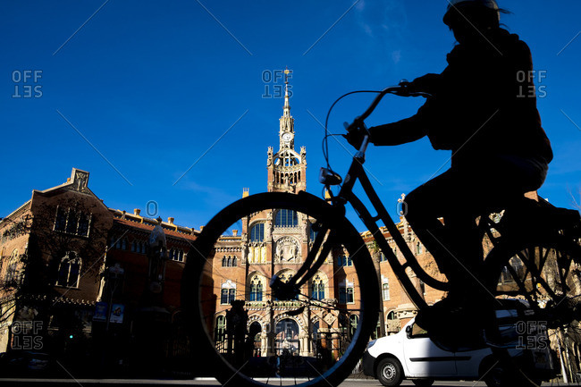 Barcelona, Spain - September 18, 2016: Bicyclist silhouetted in front of Hospital de Sant Pau