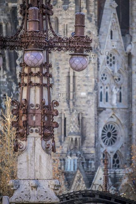 Barcelona, Spain - February 7, 2016: Gaudi's street lamp and Basilica de la Sagrada Familia