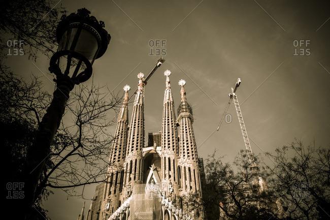Barcelona, Spain - February 7, 2016: Lamppost and cranes at Basilica de la Sagrada Familia