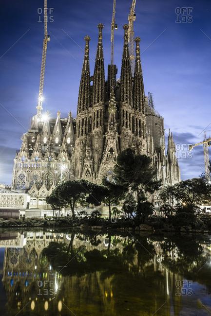 Barcelona, Spain - February 7, 2016: Sagrada Familia reflected in lake at dusk