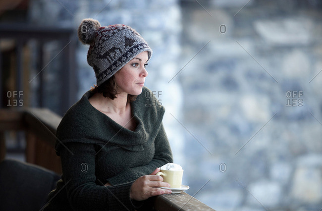 Woman with hot drink on chalet balcony