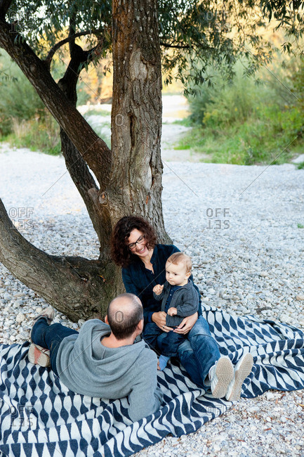 Family relaxing under tree together