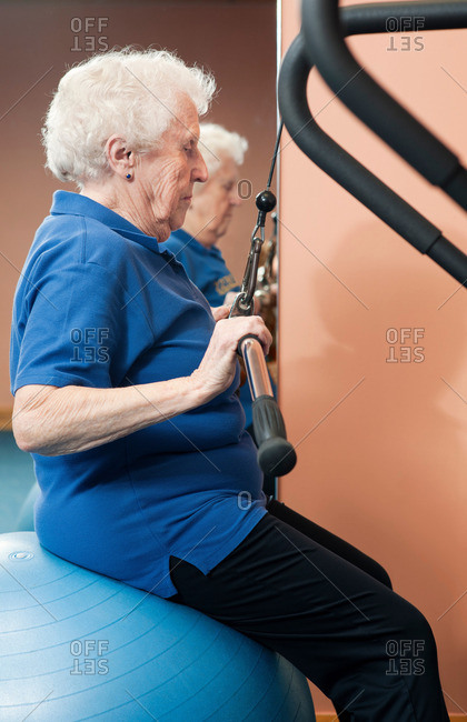 Older woman using exercise machine