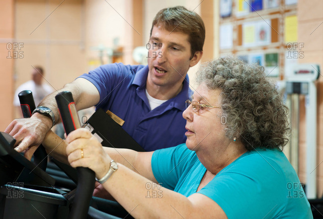 Trainer helping older woman exercise