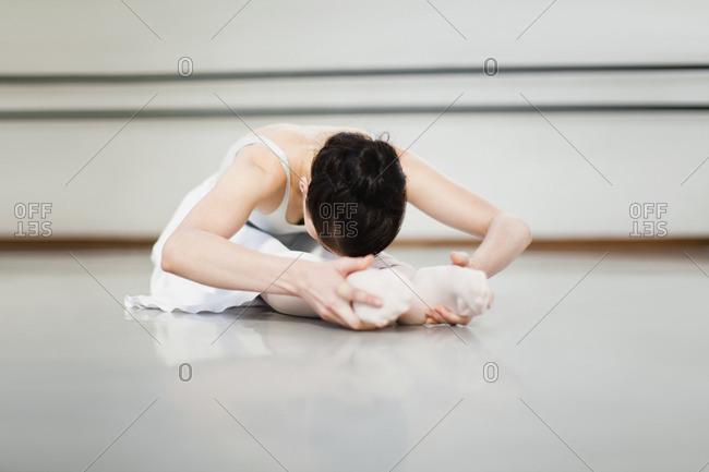 Ballet dancer stretching in studio
