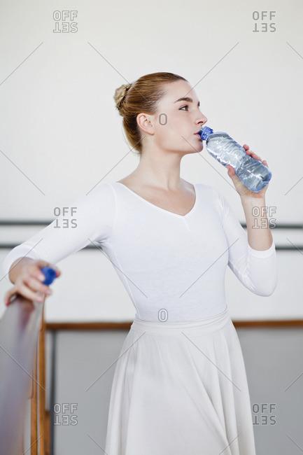 Ballet dancer drinking water in studio