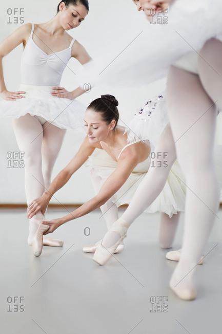 Ballet dancer adjusting colleagues pose