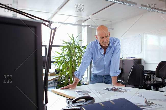 Businessman leaning over desk in office