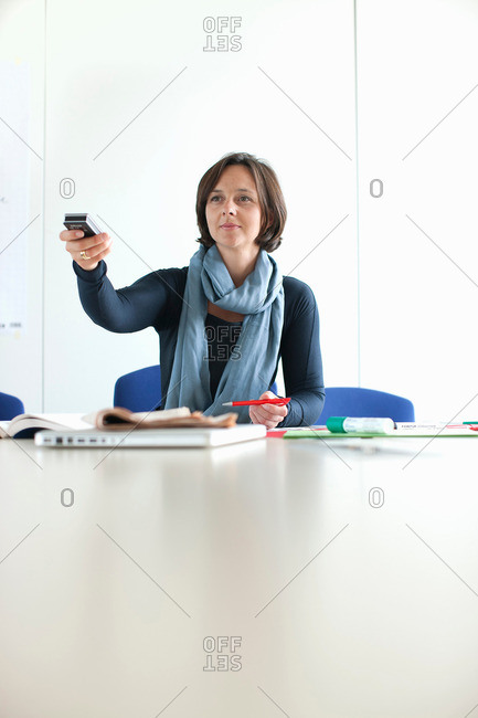 Businesswoman using remote in office