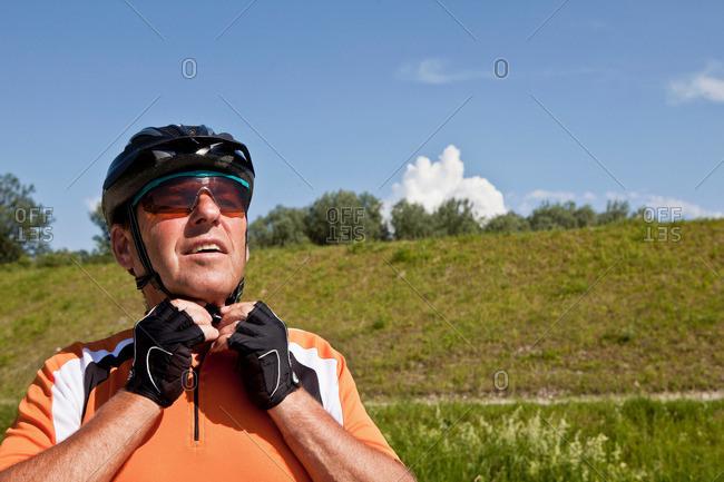 Older man fastening bike helmet