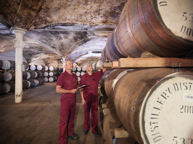 Workers checking ageing whisky barrels in distillery