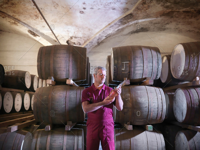 Worker with whisky bottle next to ageing whisky barrels in distillery
