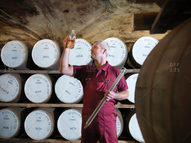 Worker with whisky sample next to ageing whisky barrels in distillery
