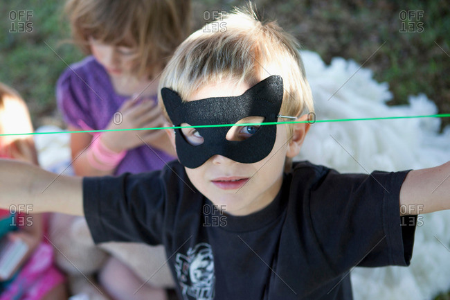 Boy wearing cat mask outdoors
