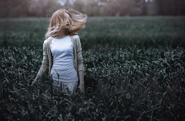 Woman tossing hair in grassy field