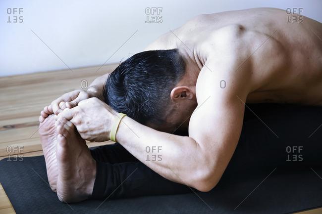 Man in yoga fold position