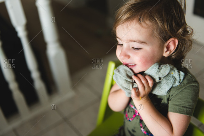 Child wiping face with cloth