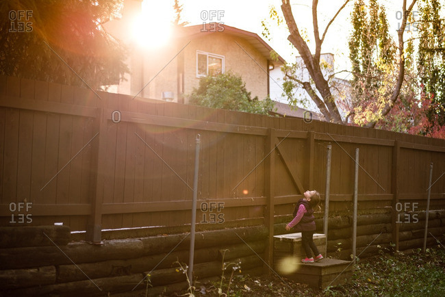 Girl looking up at home fence