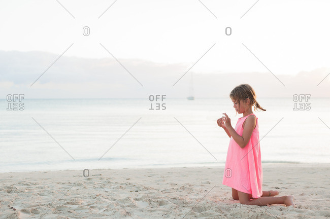 Girl kneeling on beach exploring