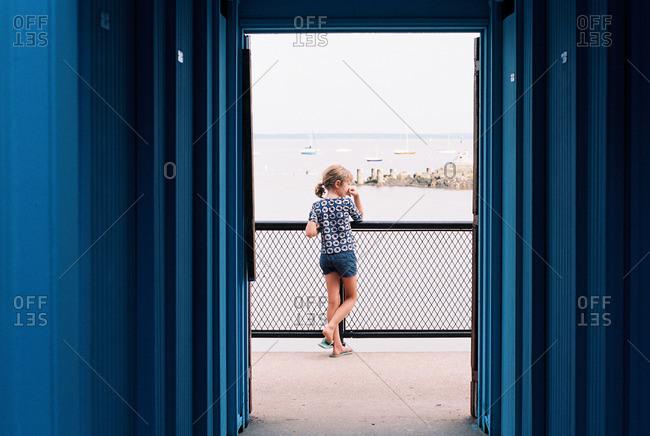 Girl staring off on coastal pier