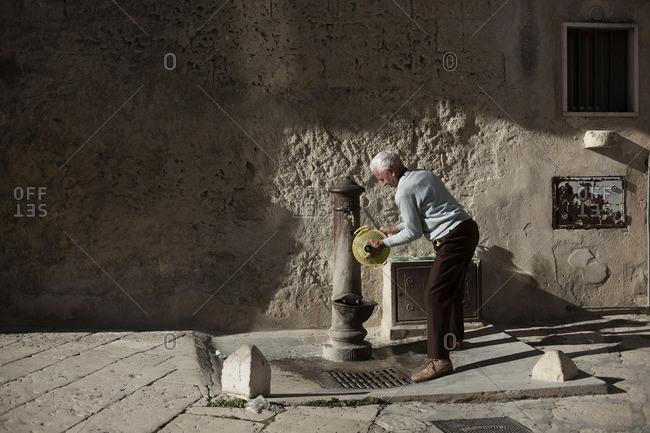 Matera, Italy - December 12, 2015: Old man washing wine bottle