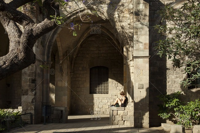 Barcelona, Spain - October 4, 2016: A girl sitting in arch of stone building