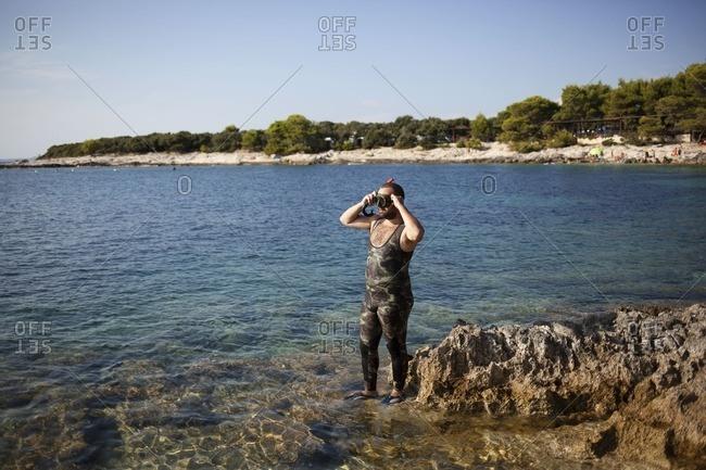 Dugi Otok, Croatia - October 4, 2016: Snorkeler on rocky shore