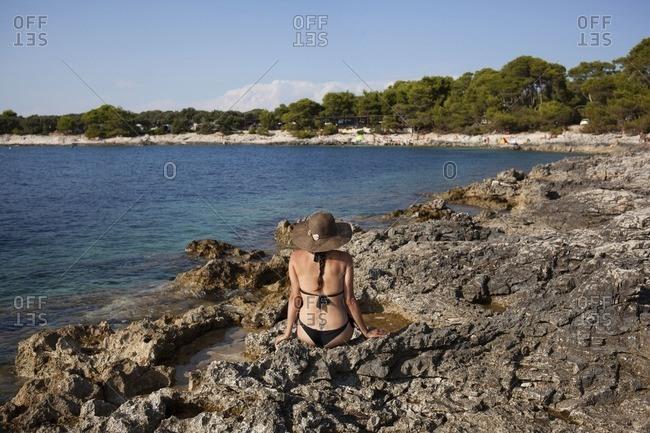 Woman in bikini on a rocky shore