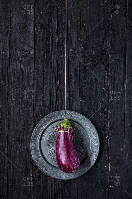 Eggplant on a string lying flat on an ornate plate