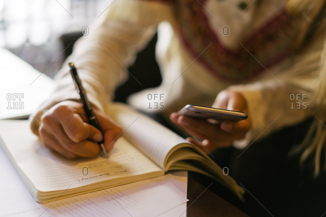 Woman writing in her journal and using a smartphone in a coffee shop