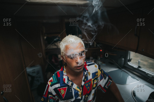 A man with bleached hair wearing a colorful shirt smoking a cigarette in a circus trailer