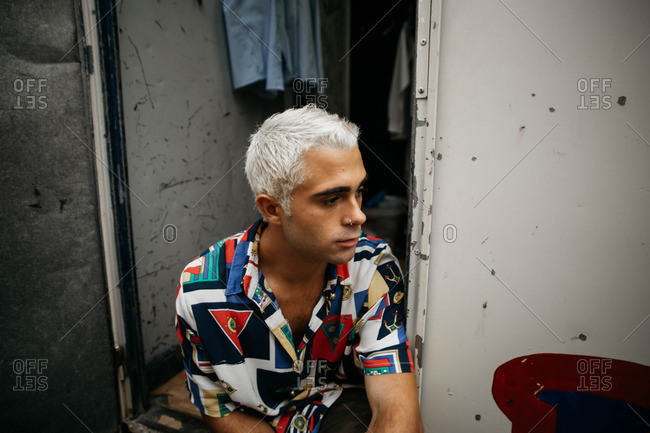 A man with bleached hair wearing a colorful shirt sitting on the steps of a circus trailer