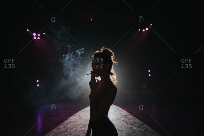 A silhouette of a woman smoking a cigarette standing in front of a projector