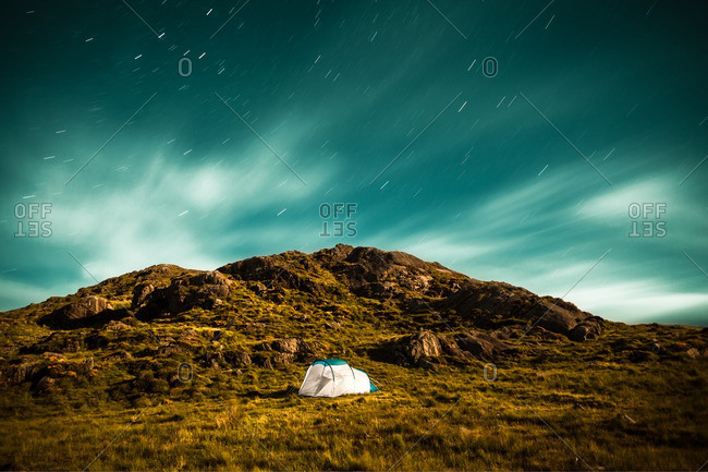 A tent pitched on a hillside under starry skies in Ireland