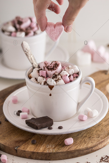 Woman placing a candy heart on top of a cup of hot chocolate with marshmallows