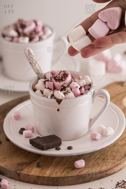 Woman placing a candy heart and marshmallows on top of a cup of hot chocolate