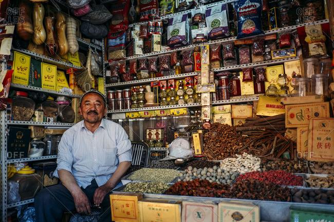 Kashgar, China - May 7, 2016: Uighur man sitting in his tea shop at a local market in old Kashgar
